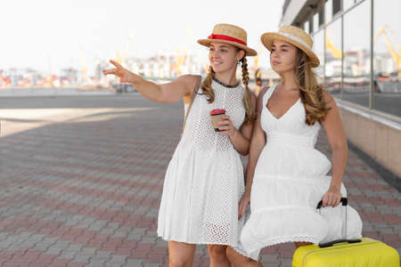 Travel and tourism concept. Two beautiful and cheerful girls-tourists in hats and with takeaway coffee go with a suitcase around the airport building.
