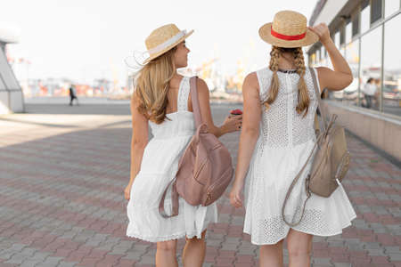 Two sisters travel with backpacks. Tourists girls in white dresses and hats on their heads talk and walk along the road in search of a hotel to relax.