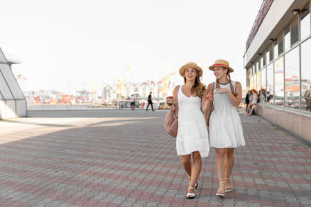 Sister travelers in hats walk along the airport with backpacks. One girl has a glass of coffee and they are in white summer dresses and light sandals.