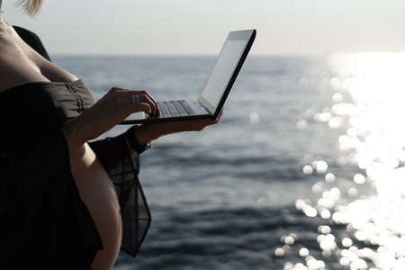 close-up of a pregnant woman's hand typing text on a laptop. Place for your text.