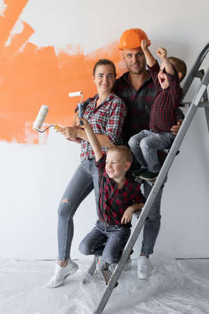 big family four people mom dad and two boys are sitting on the stairs. Home renovation concept