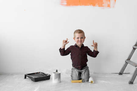 A young boy with a smile sits in a room near the stairs. Holds the paint roller in his hands with the index finger lifted up. Home renovation concept.