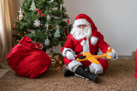 Santa Claus sits on the floor near the Christmas tree, untied the bag and took out a toy airplane gift. He was tired and sat down to rest. Holidays.