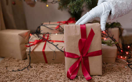 The male hand of Santa Claus in a white glove puts a gift under the Christmas tree. Christmas eve and boxes with gifts for children. The concept of the holiday and new year.