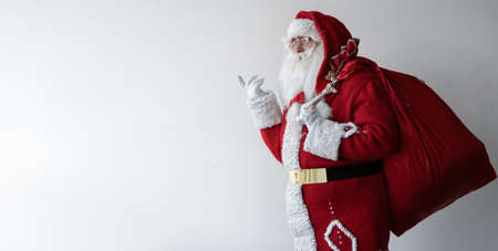 santa claus is standing on white, holding a large bag behind his back and thinking about something. Copy space