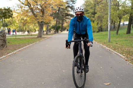 A man in a protective mask and helmet rides a bicycle on the road. Active rest in quarantine. Fighting excess weight. Place for your text.