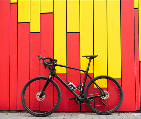 A black metal bicycle stands on the street near a bright wall. Bicycle garage. Sports in people's lives. Place for your text.