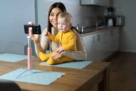 Happy mom and baby are photographed on a mobile phone, sitting in the kitchen in front of the table. The boy is sitting and smiling at the camera. Little model poses for a photo.