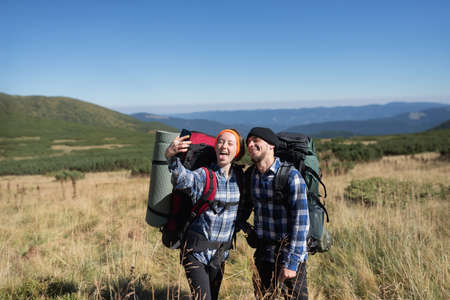 couple in love tourists man and woman stand on a mountain plain taking a selfie on their smartphone. Get out and show your tongue. Stock Photo