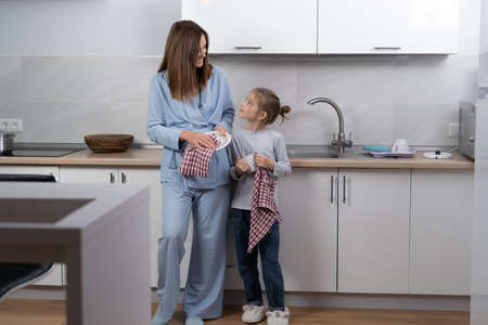 Beautiful young woman with her daughter in the kitchen wipes the dishes, looks at each other and smiles while cleaning Stock Photo