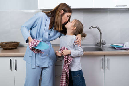 mom and daughter together in the kitchen wipe the dishes with towels. look at each other and kiss. parenting help concept.