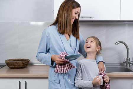 mom and daughter together in the kitchen wipe the dishes with towels. parenting help concept.