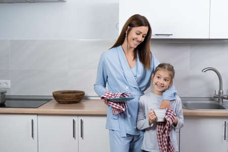 mom and daughter together in the kitchen wipe the dishes with towels. look at each other and smile. parenting help concept.
