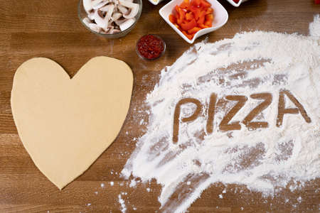 On the table in a pizzeria there is a heart-shaped pizza blank and ingredients for cooking. The flour crumbles and there is an inscription on it. Surprise for Valentines Day.