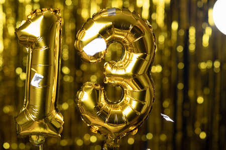 Gold foil number 13 thirteen festive balloon on a yellow background. The concept of birthday, anniversary, date.