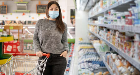 A girl in a protective mask stands with a shopping trolley near refrigerators with dairy products in a grocery supermarket.