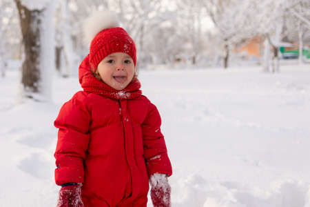 Portrait of a little girl 3 years old in mittens, a red jacket and a knitted hat, who stands in a snowy park in winter. Snow and children. Banque d'images