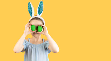 Happy Easter, kids. A girl in rabbit ears on her head holds two decorated eggs in her hands and closes her eyes with them. Baner,