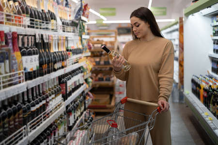 young Caucasian woman in a supermarket stands near the trolley and chooses wine. Foto de archivo