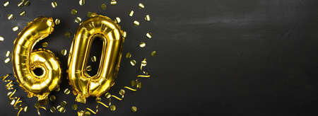 gold foil balloon number sixty. Birthday or anniversary card with the inscription 60. Black concrete background. Anniversary celebration. Banner. copy space