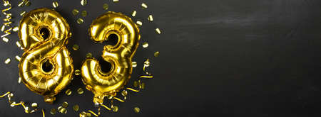 golden foil balloon number eighty three. Birthday or anniversary card with the inscription 83. Black concrete background. Anniversary celebration. Banner. Copy space