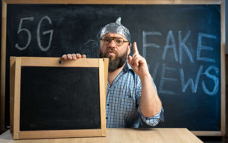 A conspiracy theorist in a protective aluminum foil hat and glasses sits at a table and points his finger at a whiteboard. Fake news concept. Conspiracy theory symbol. Mind control. Stock Photo
