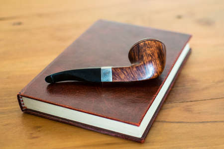 Smoking pipe on a book