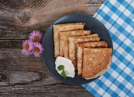 pancakes with sour cream on old wooden Board