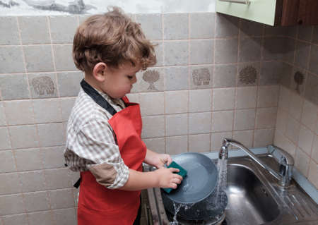 boy European appearance of the house washes the dishes in the sink