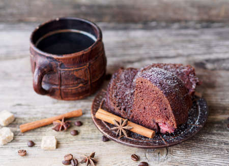 chocolate cupcake with strawberries and a large ceramic coffee mug on a wooden table Reklamní fotografie
