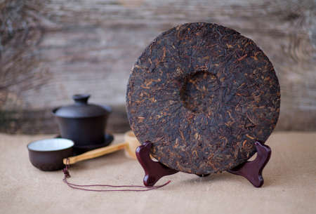 Chinese tea ripe Puer in the form of a round pancake on the table Stock fotó