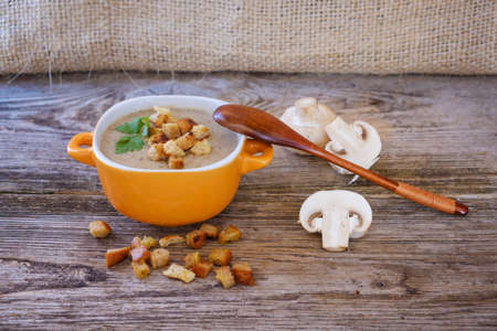 Soup puree with mushrooms and croutons in an orange bowl on a wooden table