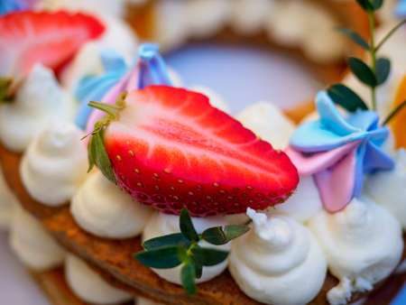Homemade cake with cream and strawberries in the form of figures eight Stock Photo