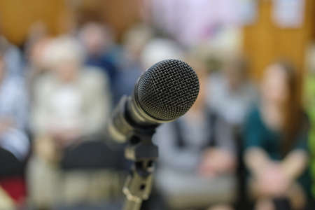 Microphone in concert hall or conference room with defocused bokeh lights in background. Extremely shallow dof. People in blur Stock Photo