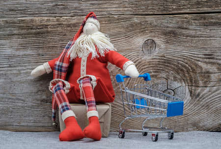 rag doll Santa Claus with a metal trolley supermarket. the concept of purchasing Christmas gifts Stock Photo - 114356014