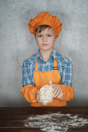 European boy dressed as a cook is engaged in cooking homemade pizza. rolls out the dough, lays out the sausage and tomatoes