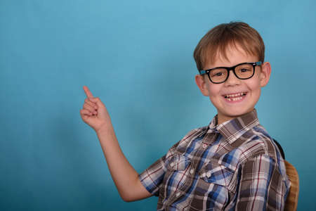 a cute European boy with glasses points his finger at an empty background . blank for design and advertising on blue background Stock Photo