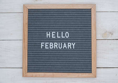English text Hello February on a letter Board in white letters on a gray background. letter Board on white wooden background