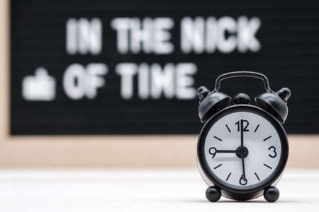 black vintage alarm clock on the background of signs with the inscription in English in the nick of time