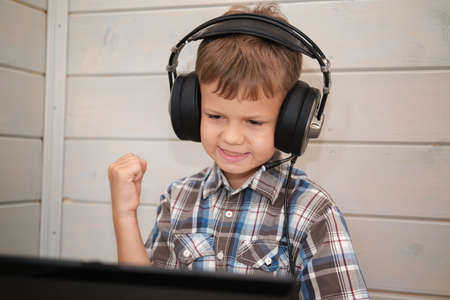 cute European boy in headphones with a microphone happily throws his hands up sitting on a laptop. the boy plays computer games. communication via Internet