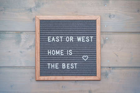 "Grey lettering Board with felt coating in wooden frame with English text "" East or West - home is the best"" on the wall of wooden house"