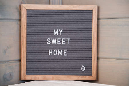 Grey lettering Board with felt coating in wooden frame with English text my sweet home in corner of wooden house