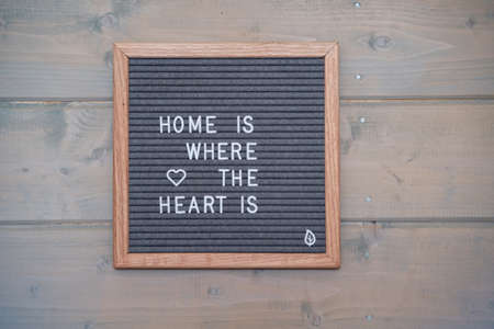 Grey lettering Board with felt coating in wooden frame with English text home is where the heart on the wall of wooden house