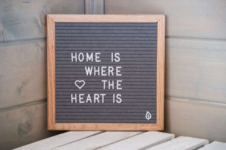 Grey lettering Board with felt coating in wooden frame with English text home is where the heart is in corner of wooden house
