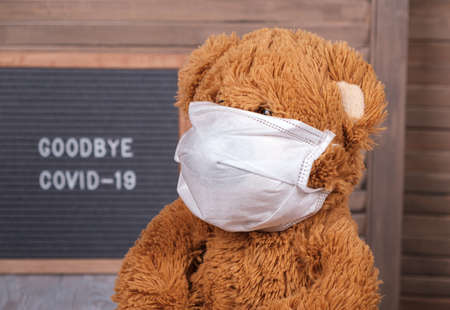 a cute Teddy bear in a medical mask sits at home against the background of a wind Board with the text in English goodbye covid-19. concept of the end of the coronavirus pandemic in the world Standard-Bild