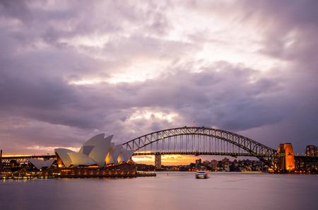 Sydney, Australia - July 11, 2010   Dramatic sky and the Sydney Opera House at dusk  Sydney skyline taken from Mrs  Macquarie s Point