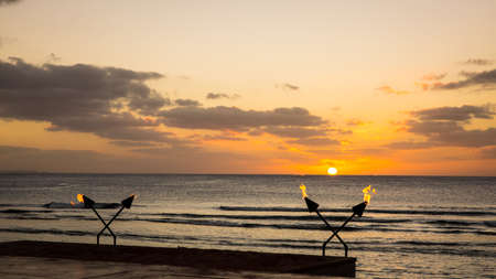 Flaming torch with sunset above the sea in Guam.