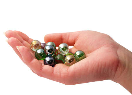 A womans hand holding shiny glass marbles Stock Photo
