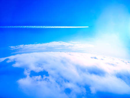 Earth from above the clouds and passing by airplane smoke trails (condensation trails)     Stock Photo