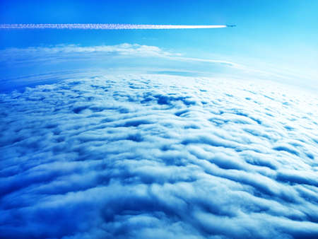 Jet plane contrail in blue sky above the thick dark clouds